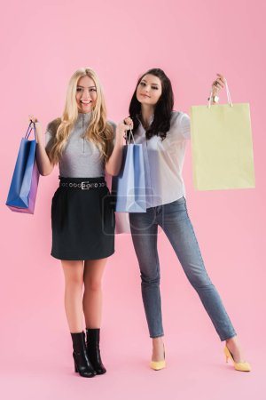 Pretty girls in good mood holding shopping bags on pink background