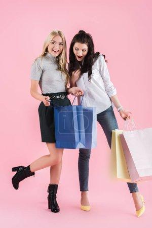 Foto de Chicas entusiastas de bolsas en fondo rosa - Imagen libre de derechos