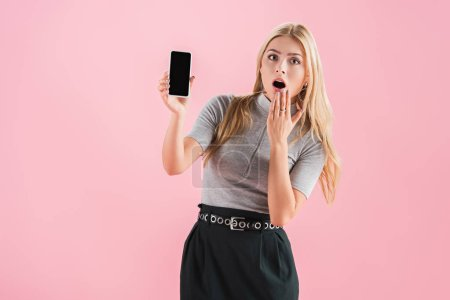 Photo for Beautiful shocked woman showing smartphone with blank screen, isolated on pink - Royalty Free Image
