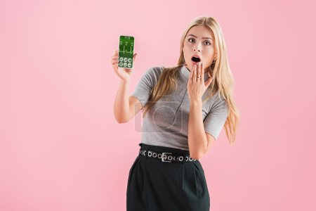 Photo for Shocked woman showing smartphone with health data on screen, isolated on pink - Royalty Free Image