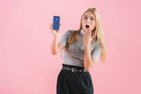 Photo for Attractive shocked girl showing smartphone with facebook app on screen, isolated on pink - Royalty Free Image