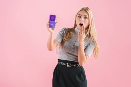 Photo for Shocked woman showing smartphone with shopping app on screen, isolated on pink - Royalty Free Image