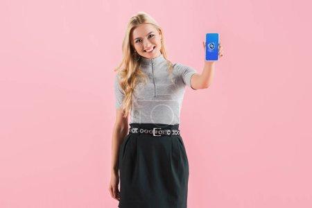 Photo pour Joyeuse fille blonde montrant smartphone avec application shazam à l'écran, isolé sur rose - image libre de droit