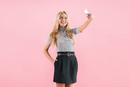 Photo pour Jolie fille blonde souriante et prenant selfie sur smartphone, isolé sur pink - image libre de droit