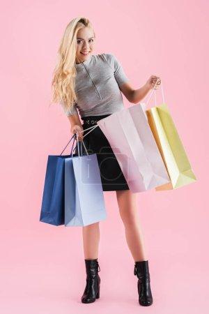 Photo pour Attrayante femme blonde portant les sacs shopping, isolés sur pink - image libre de droit