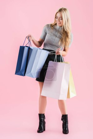 Photo for Beautiful smiling girl looking into shopping bags, isolated on pink - Royalty Free Image