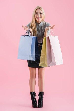 Photo pour Belle femme heureuse holding sacs à provisions, isolés sur pink - image libre de droit