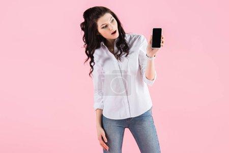 Photo pour Surprise fille brune montrant smartphone avec écran vide, isolé sur rose - image libre de droit