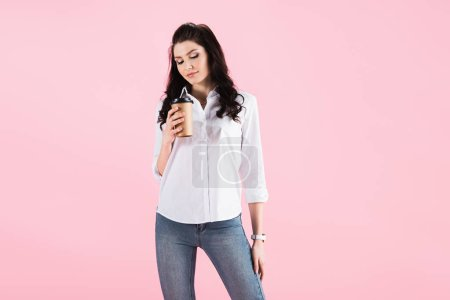 attractive woman holding coffee to go, isolated on pink