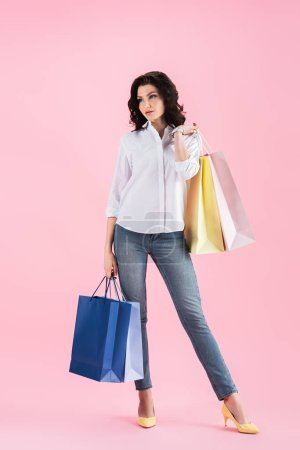 Photo for Beautiful young woman holding shopping bags, isolated on pink - Royalty Free Image