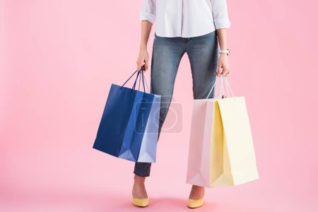 Photo pour Vue recadrée de fille tenant des sacs à provisions, isolés sur Rose - image libre de droit