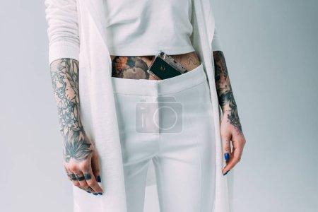 Photo pour Vue recadrée de femme avec des tatouages permanent avec une bande sonore dans pantalon isolé sur fond gris - image libre de droit