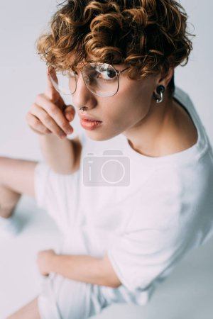 Photo for Man with curly hair sittting in glasses isolated on grey - Royalty Free Image
