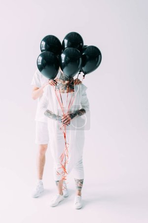 Photo for Boyfriend and girlfriend hiding behind black balloons on grey background - Royalty Free Image