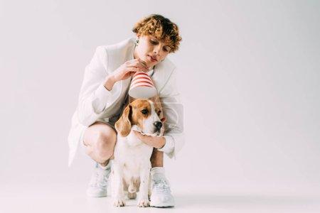 Photo pour Homme gai avec des cheveux bouclés portant casquette de fête sur chien beagle sur fond gris - image libre de droit