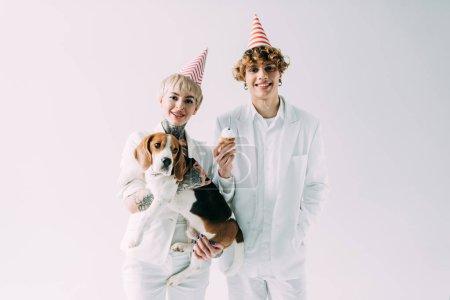 Photo pour Femme joyeuse tenant en chien beagle mignon bras en position debout avec son petit ami en partie caps isolé sur fond gris - image libre de droit