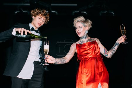 Photo for Handsome man with curly hair pouring champagne into glass of blonde woman in red dress  on black background - Royalty Free Image