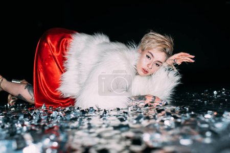 Photo for Attractive woman with tattooslying in floor with confetti isolated on black - Royalty Free Image