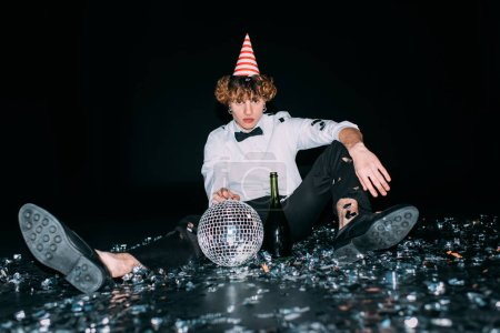 Photo for Man with curly hair sitting in party cap with disco ball isolated on black - Royalty Free Image