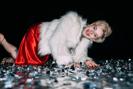 Photo for Cheerful blonde woman with tattoos lying in floor with confetti isolated on black - Royalty Free Image