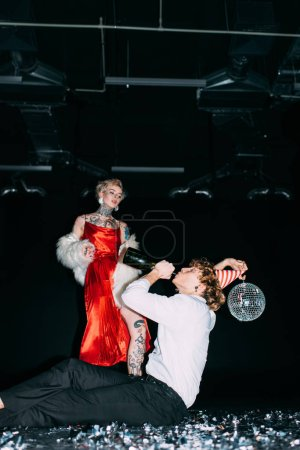 Photo for Blonde woman looking at man holding disco ball and drinking from bottle on black background - Royalty Free Image