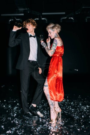 Photo for Man drinking from bottle while standing near woman with glass of alcohol drink on party isolated on black - Royalty Free Image