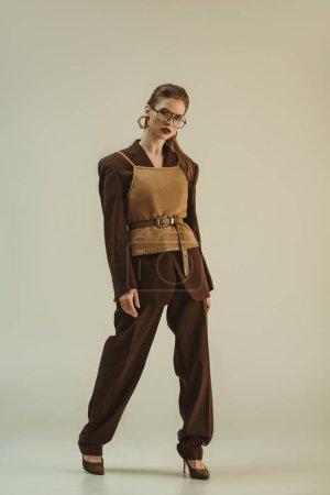 Photo pour Modèle à la mode, posant dans des vêtements à la mode rétro sur beige - image libre de droit