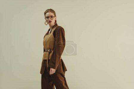 Foto de Hermosa mujer posando en ropa retro de moda moda para disparar aislado en beige - Imagen libre de derechos