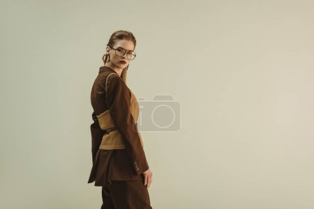 Photo for Attractive girl posing in trendy vintage clothing for fashion shoot isolated on beige - Royalty Free Image