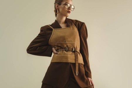 Photo for Stylish model posing in trendy retro clothing for fashion shoot isolated on beige - Royalty Free Image