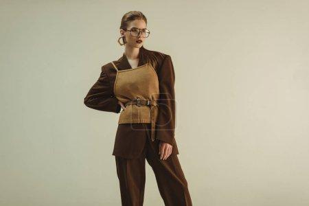 Foto de Mujer joven posando en ropa retro de moda moda para disparar aislado en beige - Imagen libre de derechos