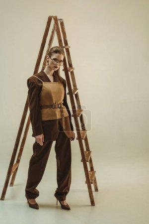Photo pour Femme attrayante dans le style vintage posant près de l'échelle en bois sur beige - image libre de droit