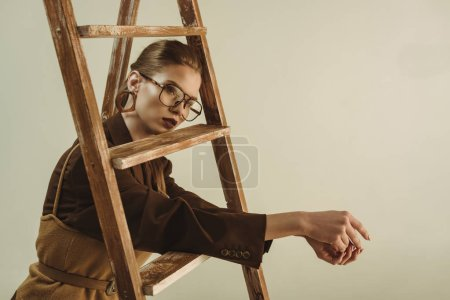Photo for Fashionable young woman in retro style posing near wooden ladder isolated on beige - Royalty Free Image