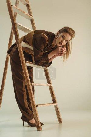 Foto de Hermosa mujer joven en estilo vintage posando junto a la escalera de madera en color beige - Imagen libre de derechos
