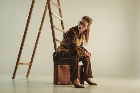 Photo pour Belle femme élégante assise sur une valise vintage près de l'échelle sur beige - image libre de droit