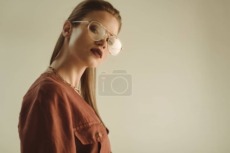 Photo for Beautiful stylish girl posing in trendy eyeglasses isolated on beige - Royalty Free Image