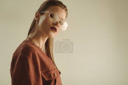 Photo pour Belle femme élégante qui pose en lunettes dernier cris isolés sur beige - image libre de droit
