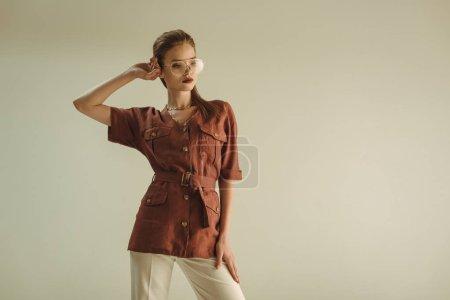 attrayant femme à la mode dans des vêtements vintage posant isolé sur beige