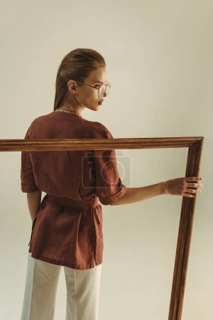 Photo for Stylish model in vintage style posing with big wooden frame isolated on beige - Royalty Free Image