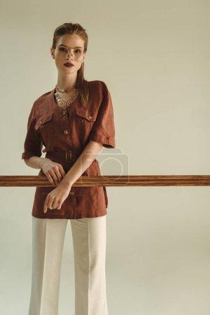 Photo pour Attrayant femme à la mode posant avec grand cadre en bois isolé sur beige - image libre de droit