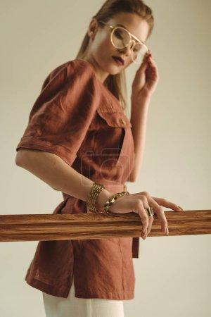 Photo pour Foyer sélectif de fille à la mode posant avec cadre en bois isolé sur beige - image libre de droit