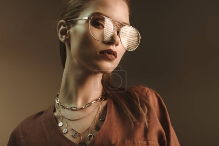 Photo for Beautiful stylish woman posing in trendy glasses isolated on brown - Royalty Free Image