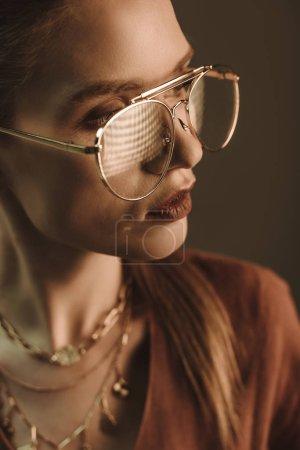 Photo pour Attrayant femme à la mode posant dans des lunettes isolées sur brun - image libre de droit