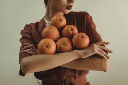 Foto de Vista recortada de chica elegante con naranjas frescas aisladas sobre beige - Imagen libre de derechos