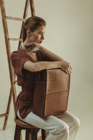 Photo pour Élégant jeune femme tenant sac en cuir et assis près de l'échelle isolé sur beige - image libre de droit