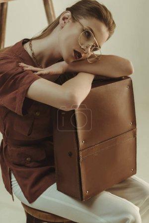 Photo pour Attrayant modèle tenant sac en cuir et assis près de l'échelle isolé sur beige - image libre de droit