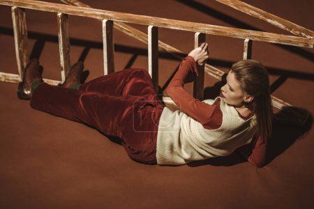Photo pour Jolie jeune fille dans un style rétro posant près d'une échelle en bois sur brown - image libre de droit