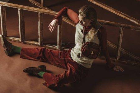 Foto de Atractivo modelo en estilo vintage posando junto a la escalera de madera en marrón - Imagen libre de derechos