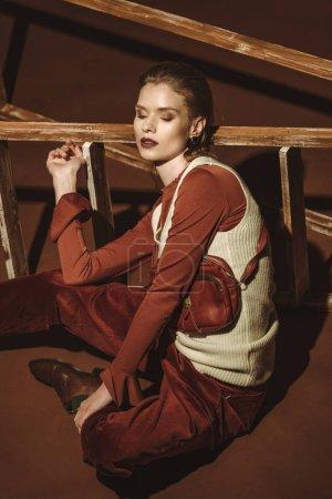 Foto de Mujer hermosa en estilo vintage posando junto a la escalera de madera en marrón - Imagen libre de derechos