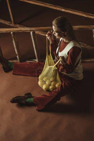 Photo pour Belle fille avec des citrons dans un sac à ficelle posant près de l'échelle - image libre de droit